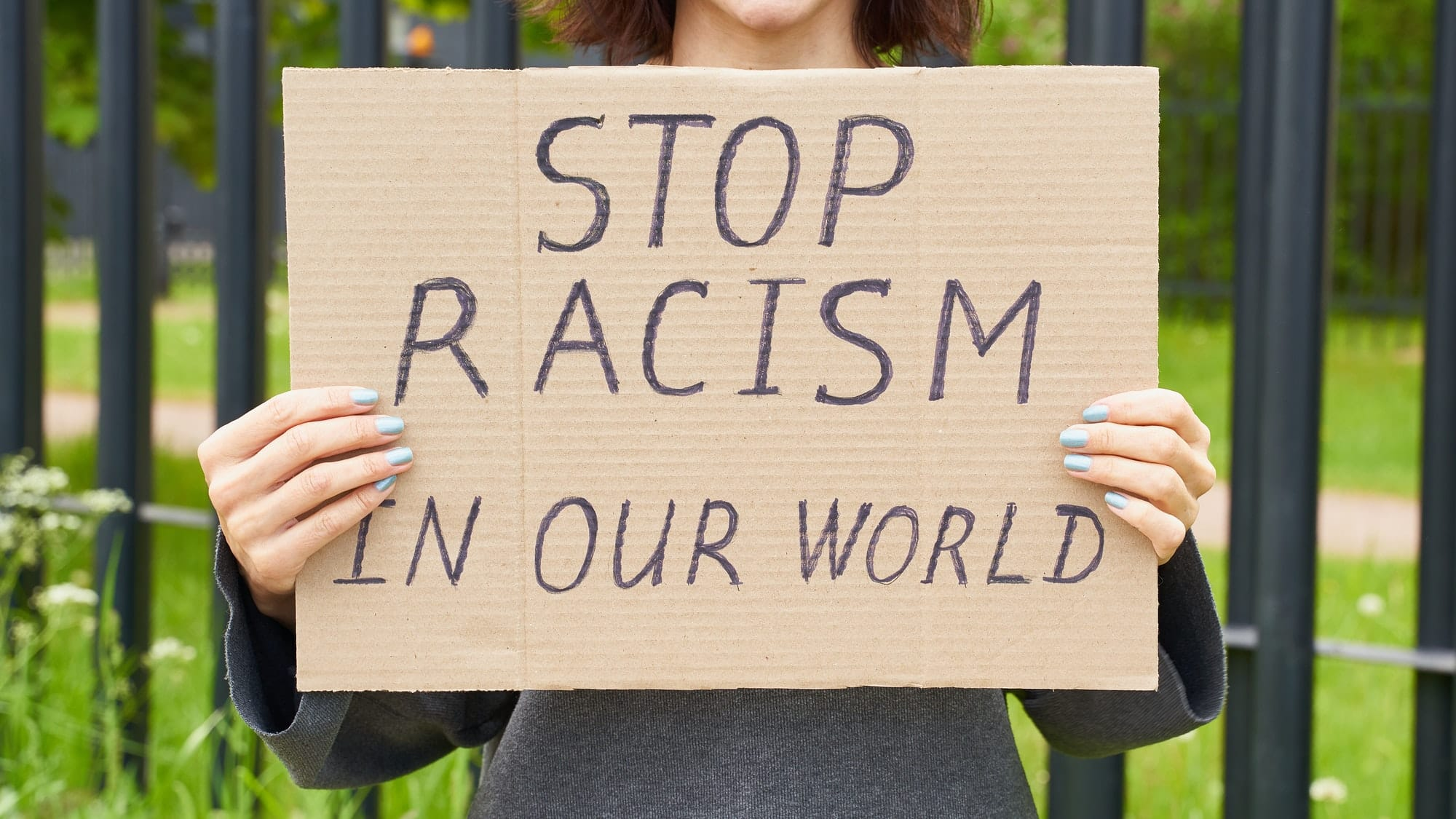 Stop racism concept. Unrecognizable white person holds sign with text against racist.