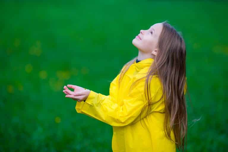 Little girl in raincoat playing in the rain outdoors